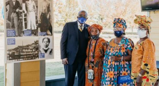 Dr. Pollard pauses for a photo opportunity with descendants of one of Oakwood's first students, Mary McBee (pictured at lower right of poster), (L-R) Dr. Pollard, Ms. Deborah Young, Ms. Hadassah Young Davis, and Ms. Judith Young.