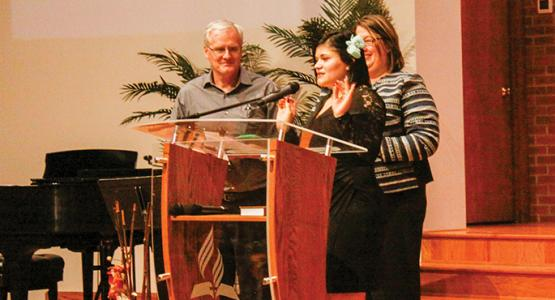 "Michelle ""Shelby"" Muyango (center), joined by Pastor John Kent and Karen Schneider, shares her testimony."