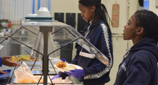 Junior Sh'Dai Forrester and freshman Miya Fields serve food in the cafeteria.