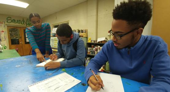 Fashion students Leigh Nebblett (middle) and Xavier Burely (right) design artwork for a class project.