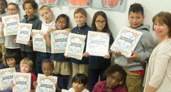 Richmond Academy first- and second-graders hold The Leader in Me notebooks, alongside teacher Karen Van Ornam.