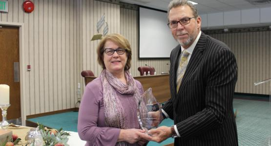 Karen Robinson accepts a Notable Person of Honor Award from Dave Weigley on behalf of her late husband, Dave