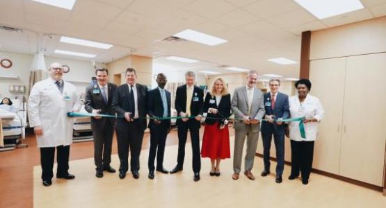Phillip Smith, IPE Sim Center Simulation Technician; Nate Brandstater, Kettering College President; John Jervis, Kettering College board member; Donovan Ross, Kettering College board member; Walter Sackett, president of Kettering Medical Center System; Dr. Paula Reams, Director of the Division of Nursing at Kettering College; Winston Baldwin, Kettering College board member; Rick Thie, president of Kettering Medical Center Foundation, and Beverly McLean, IPE Sim Center Nursing Coordinator all pose before cut