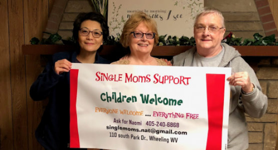 Surrounded by church members Annabel Murphy and Sue Walter, Naomi Tricomi, pastoral assistant for the Weirton/Wheeling, W.Va., district, together display an advertising banner for a Single Mom's Ministries event.
