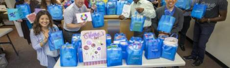 WGTS Staff poses with bags of Mother's Day cards before going out to deliver.