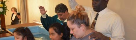 Pastor Pedro Simpson baptizes the Martinez family as  evangelist Julio Chazarreta looks on