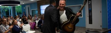 El artista Matthew West felicita al presentador y director de promociones de WGTS Morning Show, Jerry Woods, en el mini concierto de inauguración.
