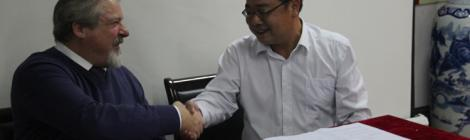 Principal Dave Morgan signs sister school agreement with Fang Wangdong of the Lin'an High School in China.