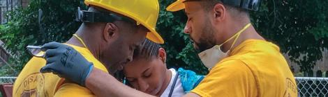 During an event to help clean up Baltimore homes impacted by recent floods, Derrick Lea (left), director of Adventist Community Services (ACS) Disaster Response (DR) at the North American Division, and David Franklin (right), pastor of Allegheny East Conference's Miracle City church in Baltimore, pray with Dionne, whose home was one of the hardest hit properties on Frederick Avenue.