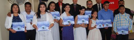 New members display their baptismal certificates.