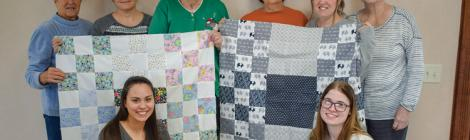 Lois Ruth (standing, second from right) and the Columbus Eastwood Women's Ministries team hold two handmade quilts for infants at a local hospital.