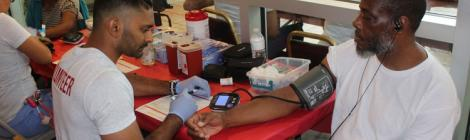 A volunteer screens a patient before he is treated. Photo by Kenneth Moore, Jr.
