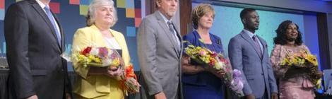 Los delegados reeligieron al presidente Dave Weigley (en la foto al centro con su esposa, Becky), al secretario ejecutivo Rick Remmers (a la izquierda con su esposa, Shayne) y al tesorero Emmanuel Asiedu (en la foto con su esposa, Annette) para el período 2021-2026.