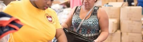 A volunteer distributes clothing at the World Harvest Outreach church in Houston. Photo by Keith Goodman