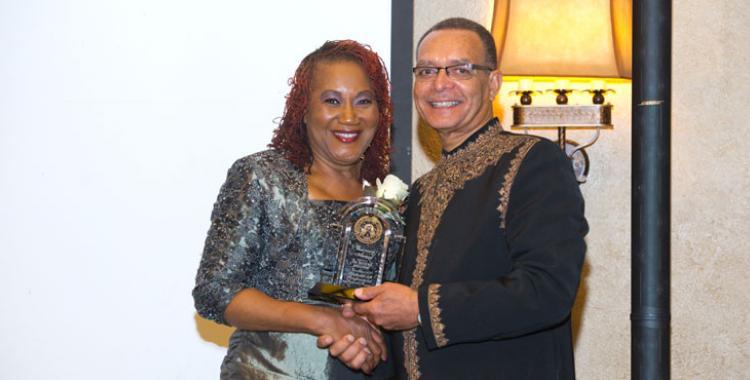 Hyveth Williams and Wymouth Spence display Williams award at WAU's Visionaries Gala.