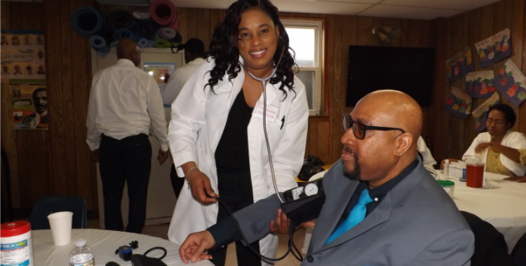 Willow Grove church member Rosemarie Webster takes blood pressure from frequent visitor Dornell LaVant during the Community Outreach Day.