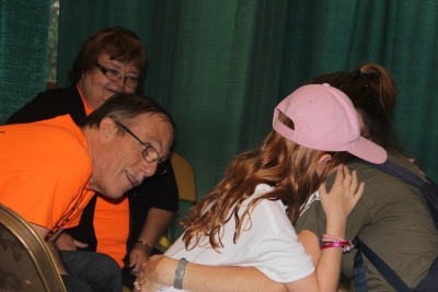Milton and Margo Chappell, members of Sligo church, comfort a crying little girl at the prayer tent.