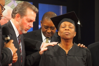 Dave Weigley (left), Columbia Union president, and Seth Bardu, Columbia Union treasurer, lay hands on Brenda Billingy, senior pastor of the Metropolitan church in Hyattsville, Md., during her surprise ordination service.